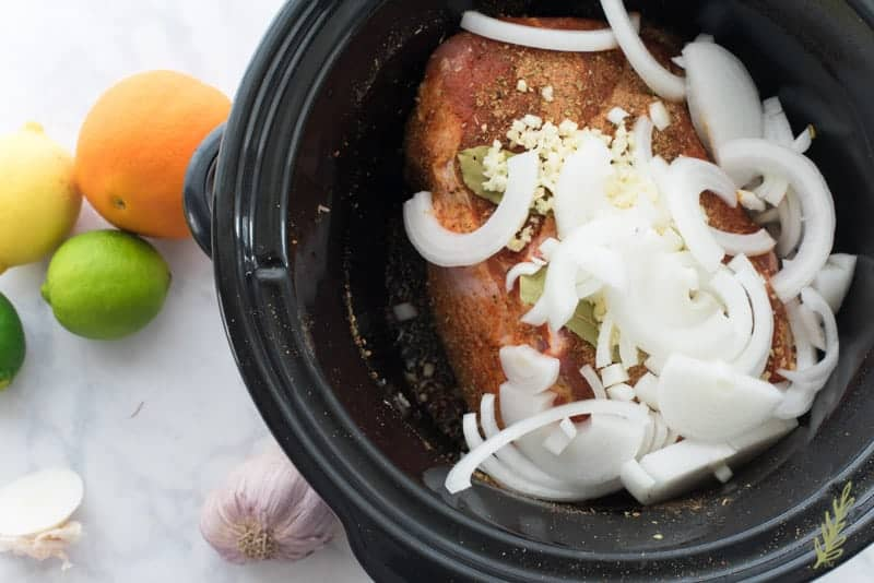 After being rubbed in the spice blend, the pork sits in the slow cooker covered in sliced onions, minced garlic, and bay leaves