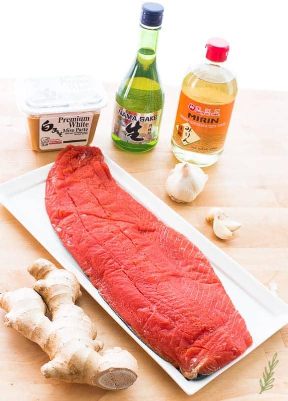 Ingredients to make Miso-Ginger Salmon: mirin, white miso, sake, salmon, garlic, and ginger on a wooden surface.