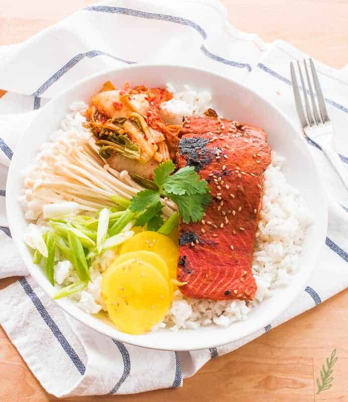 White bowl of white rice, Miso-Ginger Salmon, and accompaniments on a blue and white striped towel.