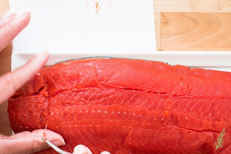 A hand uses bone tweezers to remove pin bones from a side of salmon