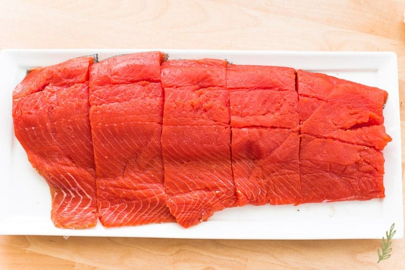 A side of salmon cut into portion sizes on a white platter