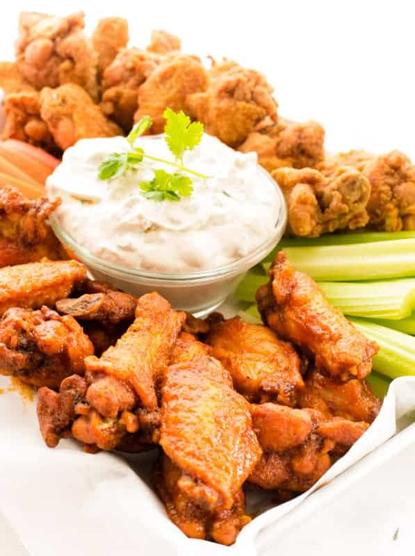 Close up image of blue cheese dipping sauce a buffalo wing in blue cheese dip. The platter of wings, carrots, and celery in background