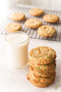 A stack of White Chocolate Chip Cookies sits next to a glass of milk