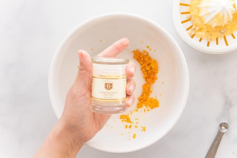 Lemon salt is held over the bowl of lemon zest