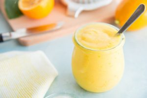 Meyer Lemon Curd in a glass jar with a silver spoon in it.
