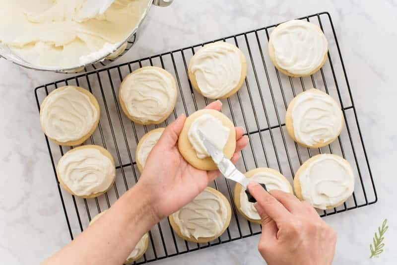 A hand smoothing frosting over a Soft Sugar Cookies with Cream Cheese Frosting
