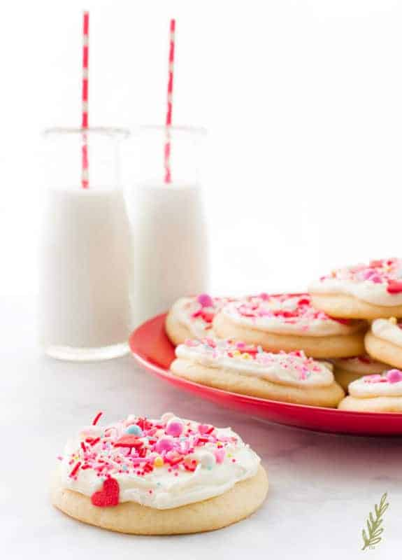 A single Soft Sugar Cookie with Cream Cheese Frosting with two glasses of milk and a plate of cookies behind Change the sprinkles for Labor Day