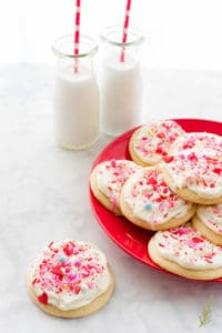 A single Soft Sugar Cookies with Cream Cheese Frosting on a white marble surface next to a red plate filled with cookies. Two glass jars of milk are next to the plater