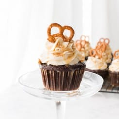 A single Chocolate Stout-Pretzel Cupcake with Bailey's Buttercream and Caramel Drizzle with more cupcakes in background