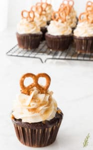 A single Chocolate Stout-Pretzel Cupcakes with Bailey's Buttercream and Caramel Drizzle in front a rack full of the cupcakes