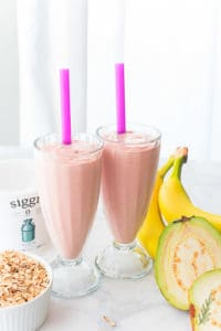 Two glasses of Guava Banana Oatmeal Breakfast Shake are surrounded by their ingredients.