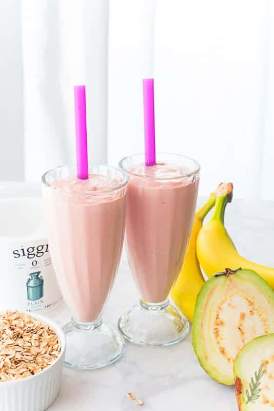 A portrait image of two Guava shakes next to the ingredients that were used to make them
