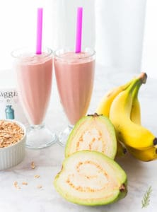 Two milkshake glasses filled with Guava Banana Oatmeal Breakfast Shake