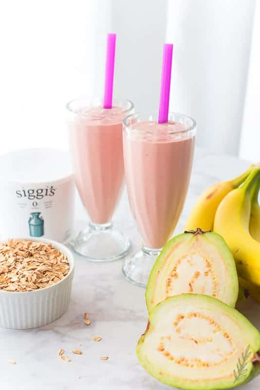 Two milkshake glasses filled with Guava Banana Oatmeal Breakfast Shake. Pink straws, Shake ingredients surround