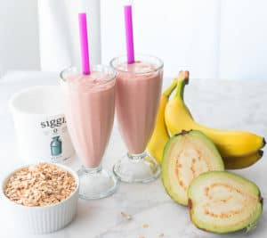 Two milkshake glasses filled with Guava Banana Oatmeal Breakfast Smoothie the ingredients surround the glasses