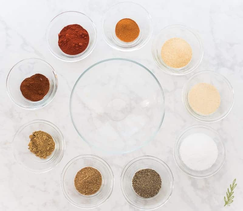 Spices in glass bowls surround a large glass mixing bowl