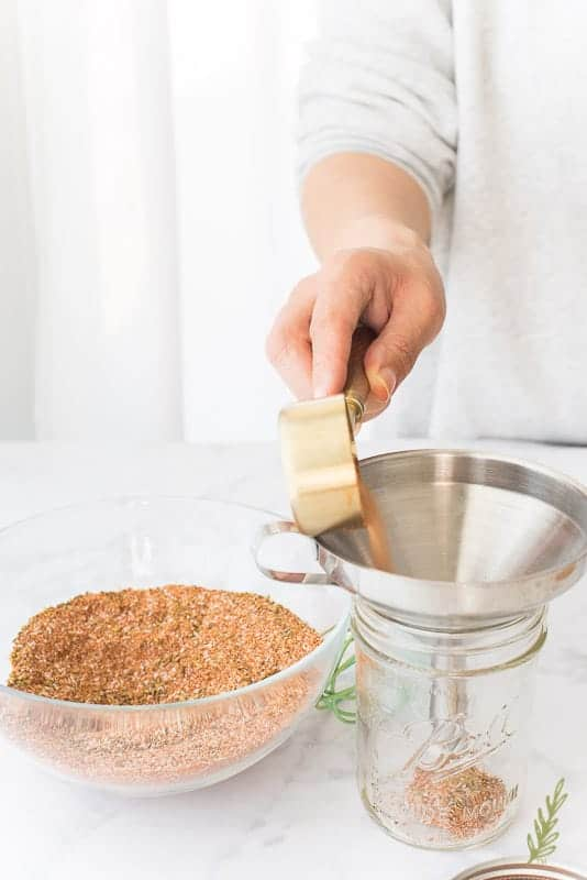 A hand pours the Meat Spice Blend through a funnel into a mason jar