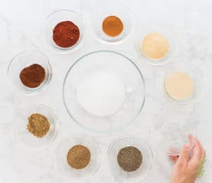 A bowl of salt is surrounded by the remaining spices used to make Meat Spice Blend