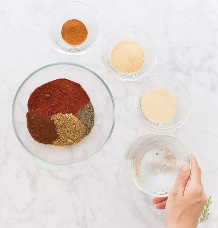 Cayenne Pepper is added to a glass bowl with other spices