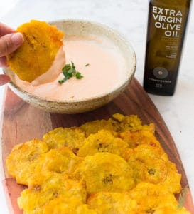 Dipping Tostones (Pan-Fried Plantains) in mayo-ketchup