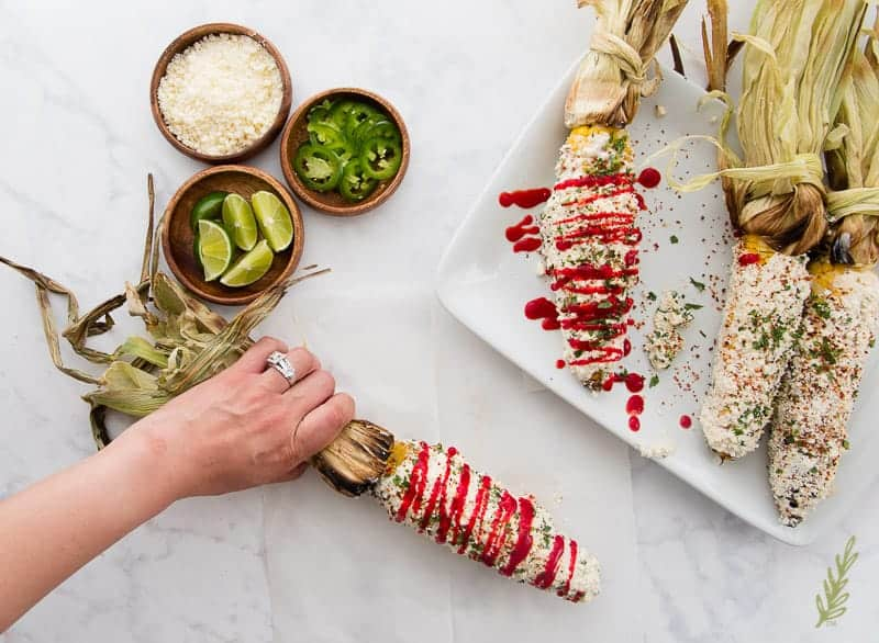 Hand grabbing an Elote (Mexican Street Corn) awesome Labor Day side dish