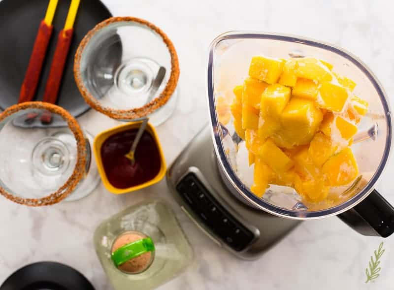 The frozen mango is added to the blender with the ice.