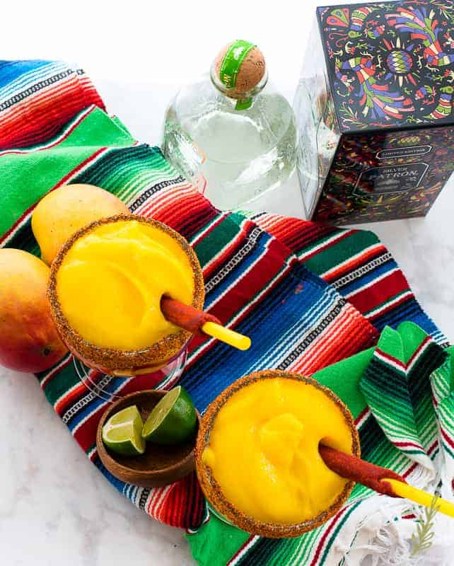The prepared mangonadas sit on a Mexican serape. A bottle and box of tequila is in top right corner. A bowl of limes is in between the two glasses and fresh mango are at top left