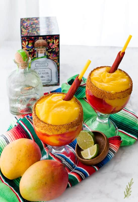 Two goblets of Mangonadas (Spiced Mango Margarita) on a serape. Two mangos are in bottom left corner. A bowl of limes is in between the glasses. A box and bottle of tequila are top left