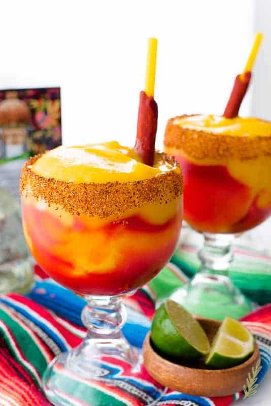 Close up image of two goblets of Mangonadas (Spiced Mango Margarita). A wooden bowl with limes is to the bottom right of the foreward goblet