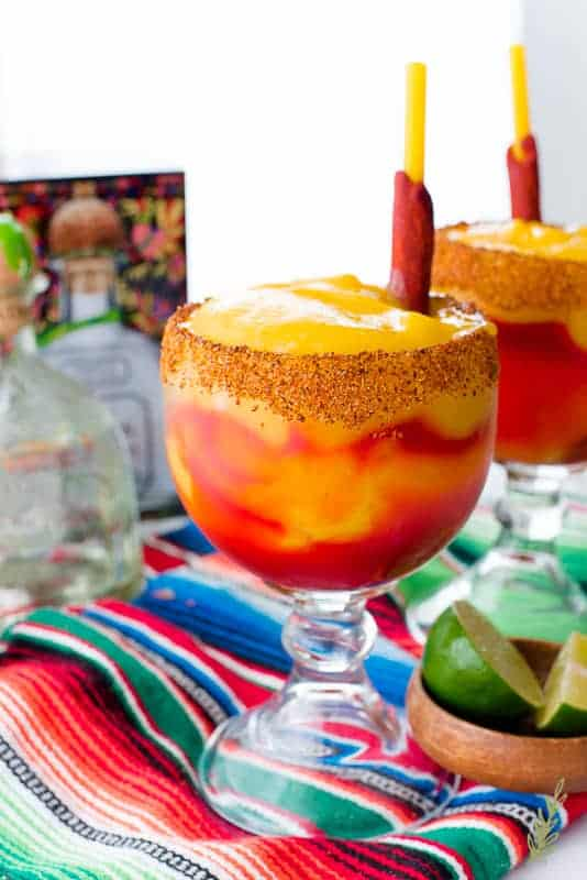 Two goblets filled with Mangonadas (Spiced Mango Margarita) on a serape. A wooden bowl of lime wedges is on the right side. A bottle of Patron tequila is in background