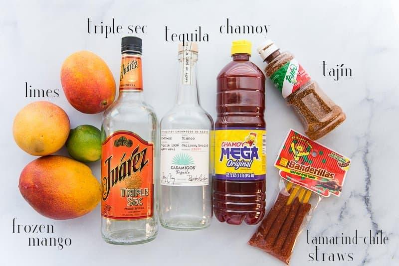 Ingredients to make mangonadas: mangos, lime, triple sec, tequila, chamoy, tajín, and tamarind chile straws