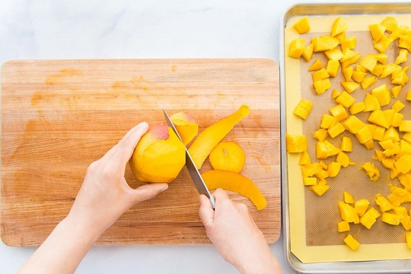 A knife is being used to peel a mango. On a wooden cutting board