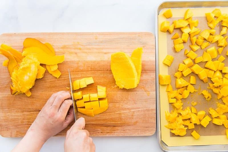 Mango flesh is cut into chunks on a wooden cutting board