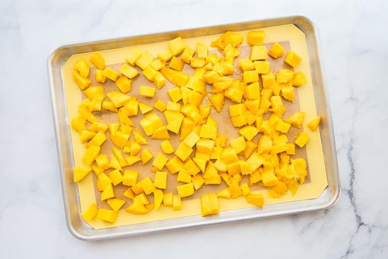 Mango chunks on a silicone lined sheetpan