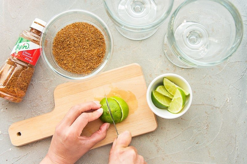 Limes being cut on a wooden cutting board.