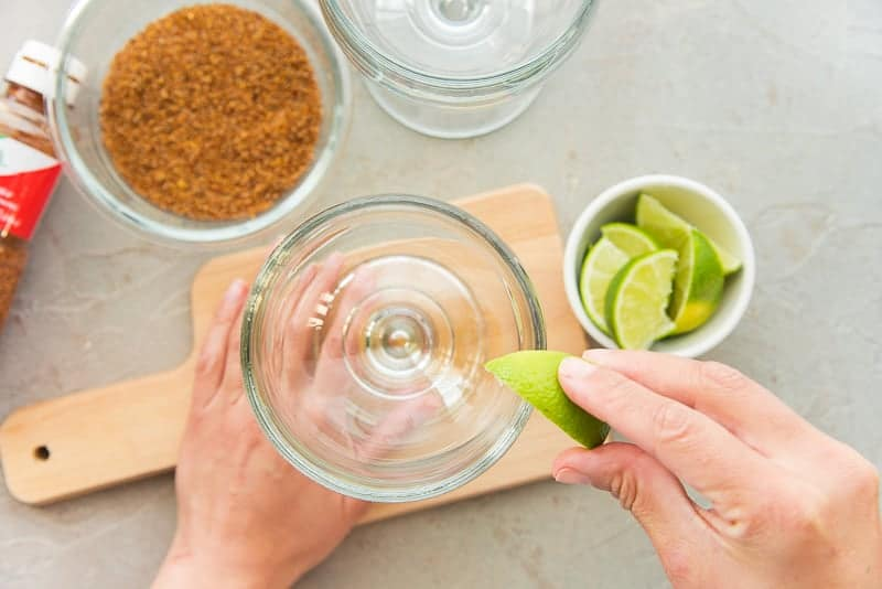 A hand uses a lime wedge to moisten the rim of the glass goblet.