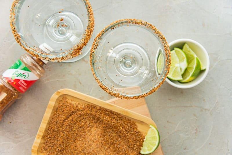 Tajín rimmed goblets next to a tray with the spice on it.