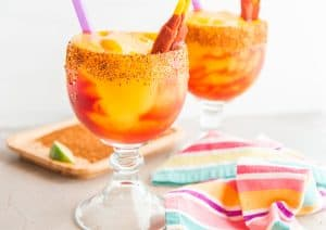 Two goblets filled with Mangonada (Spiced Mango Margarita) a grey surface