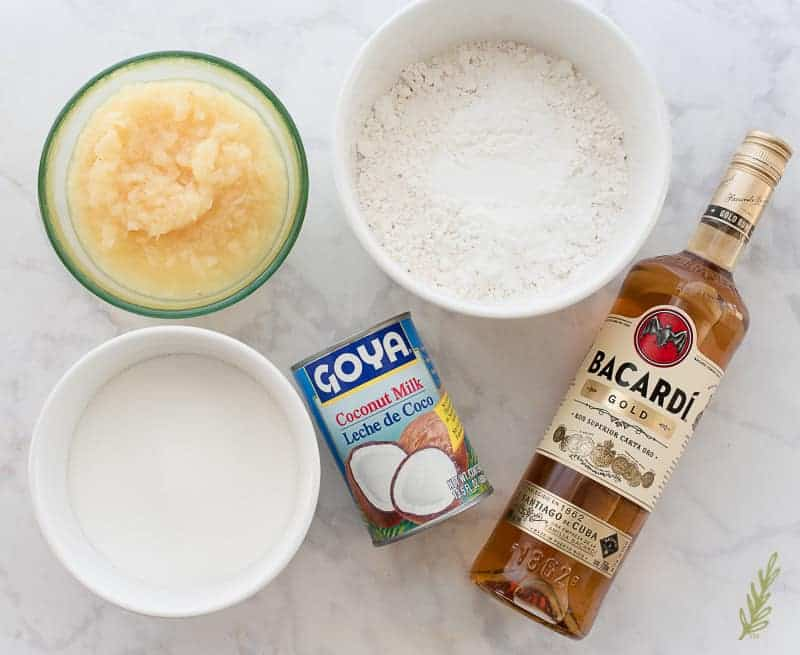 Piña Colada Cake ingredients from left to right: a white bowl of sugar, a glass bowl of crushed pineapple, a can of coconut milk, a white bowl with flour and baking powder, a bottle of gold rum