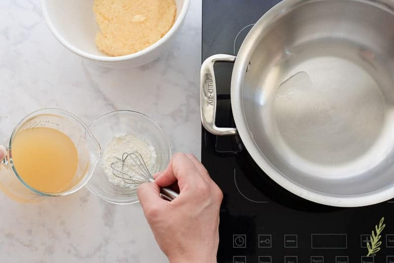 A portion of the pineapple juice-rum mix is added to a small glass bowl of cornstarch. A hand uses a whisk to mix the two together. To the right is a stainless pot on a burner. Above in a white bowl is the drained crushed pineapple.