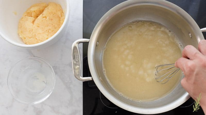 The pineapple-rum liquid is brought to a boil, then the cornstarch mixture is added to thicken it. A hand whisks the mixture in a pot.