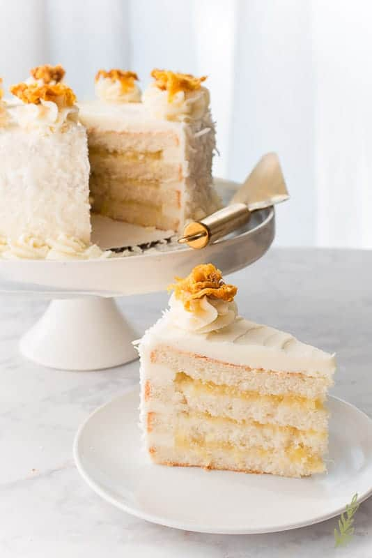 A slice of the Piña Colada Cake is one a white plate. The side is visible. The rest of the cake is the left background on a cake stand. A gold spatula is propped on the cake stand.