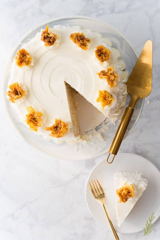 Overhead image of Piña Colada Cake with a slice removed from the cake and sitting on a white plate. A gold cake server is propped on the cake stand.