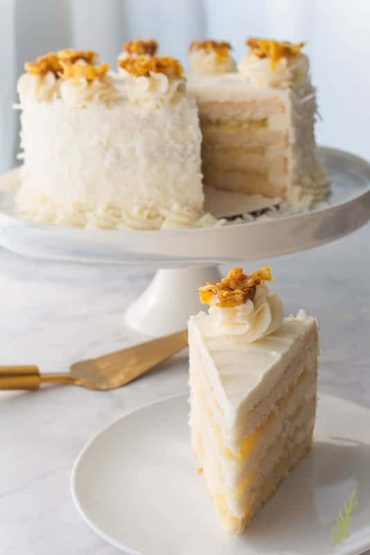 A front view of the Piña Colada Cake slice on a white plate. The rest of the cake is in the left background. A gold spatula is beneath the cake stand.