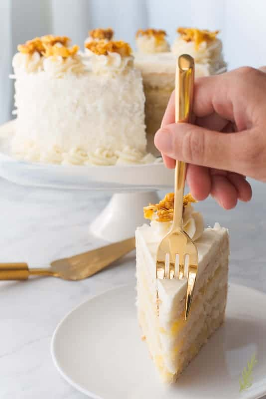 A fork digs into the slice of Piña Colada Cake, which is on a white plate. The rest of the cake can be seen in the background along with a gold cake server.