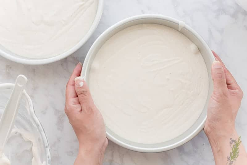 Two hands tap the pan gently against the countertop to release any air bubbles from the cake batter