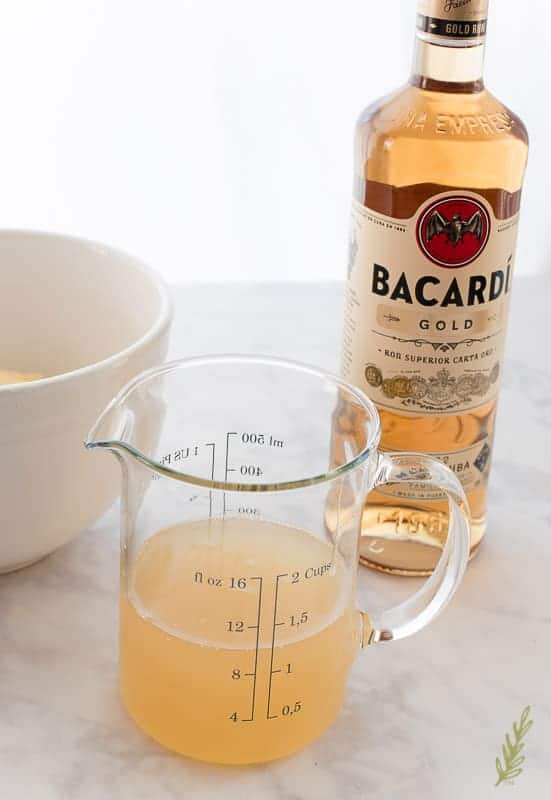 A clear, glass measuring cup filled with pineapple juice and rum sits in front of a bottle of rum which is in the background to the right.
