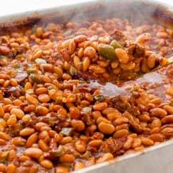 Scooping a spoonful of Texas Baked Beans out of the pan