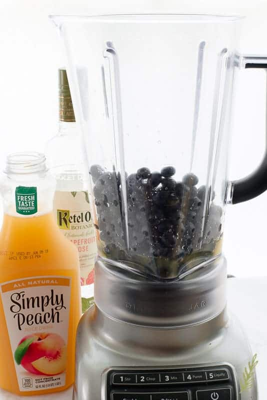 Simply Peach and Ketel One Vodka bottles next to a blender filled with blueberries