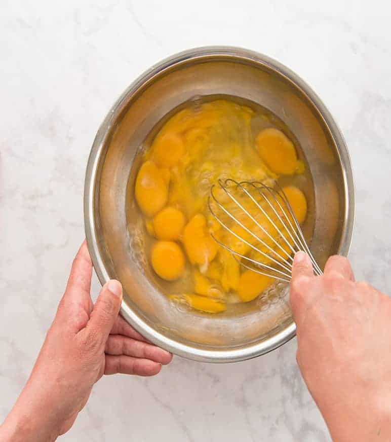 A hand whisking eggs with a silver whisk in a silver bowl